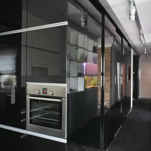 Wysoka zabudowa kuchenna z czarnymi, lakierowanymi frontami stanowi wizualną kontynuację zabudowy przedpokoju. W słupku – na wygodnej wysokości – piekarnik marki Bosch. Fot. Bartosz Jarosz.