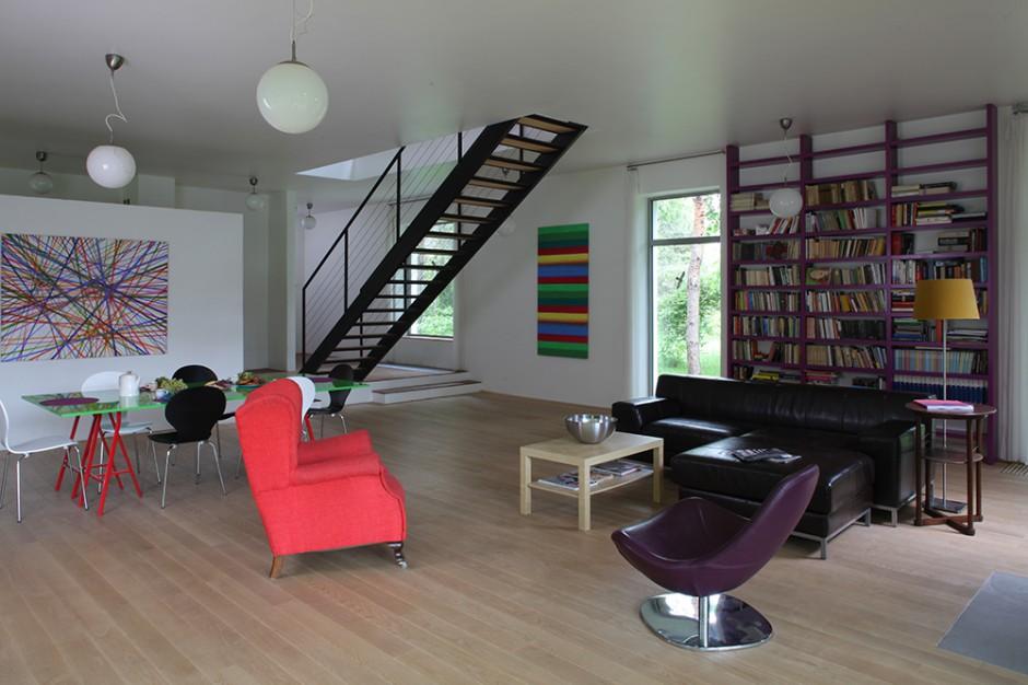 Salon to ogromna przestrzeń połączona z jadalnią. Stolik, przy którym są spożywane posiłki, regał na książki oraz struktura schodów prowadzących na piętro, powstały według koncepcji Jacka Ziemińskiego. Fot. Tomek Markowski.
