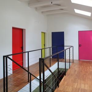 Na piętrze wejście do każdego pomieszczenia wyznacza inna barwa drzwi. W tym domu zabawa kolorem spotyka nas na każdym kroku. Fot. Tomek Markowski.