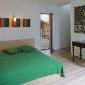 Sypialnia w drewnie idealnie wpisuje się w konstrukcję domu. Nie mogło tu także zabraknąć obrazu pana domu. Fot. Tomek Markowski.
