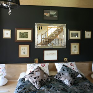 Łóżko do sypialni było zrobione na zamówienie. Nie jest to jedyny unikat w tym wnętrzu. Tuż nad zagłówkiem, na czarnym tle, galeria sztuki z prawdziwa perełką – grafiką Salvadora Dali. Fot. Bartosz Jarosz.