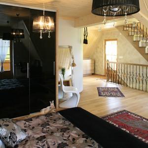 Obudowana jasnym, ciepłym drewnem sypialnia, to wnętrze ulokowane bezpośrednio na  piętrze, co zapewniło mu otwartą, dużą przestrzeń. Przytulna, naturalna baza posłużyła jako tło dla wyposażenia w ciemnym kolorze: czarnej szafy o lakierowanych frontach, tiulowych żyrandoli, narzuty na łóżko i barwnych, gruzińskich dywaników. Fot. Bartosz Jarosz.