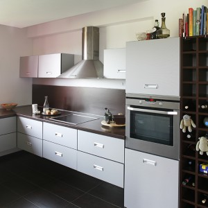 W kuchni dominującą purpurę (Dekoral) zastępuje neutralizująca stalowa szarość. Zabudowa kuchenna, wykonana przez zaprzyjaźnionego stolarza, nie tylko cieszy oko domowników, lecz przede wszystkim zapewnia komfort użytkowania i łatwość utrzymania porządku. Fot. Bartosz Jarosz.