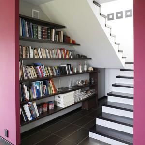 Domową biblioteczkę pomysłowo zaaranżowano pod schodami, wiodącymi na poddasze, gdzie znajduje się prywatna część domu, z dwiema sypialniami i  łazienką. Fot. Bartosz Jarosz.