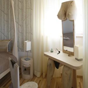Oprócz łóżka i toaletki, w sypialni pojawiają się także inne, wyrzeźbione w drewnie, meble do kompletu: okrągłe jak pniaki szafki nocne i krzesło. Fot. Bartosz Jarosz.