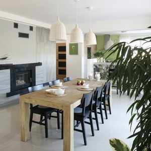 Duży stół (Meble Egzotyczne) jest sercem jadalni. Ustawiono przy nim czarne krzesła (IKEA). W sąsiedztwie kominek obłożony czarnym granitem i płytkami. Fot. Bartosz Jarosz.