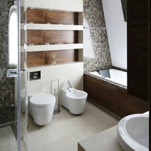 Prywatna łazienka na poddaszu za sprawą ciemnobrązowych drewnianych akcentów wykończenia idealnie koresponduje z koncepcją całego domu. Nawet toaleta i bidet marki Duravit zostały dobrane tak, by kulisty, opływowy kształt został w pełni zachowany. Fot. Bartosz Jarosz.
