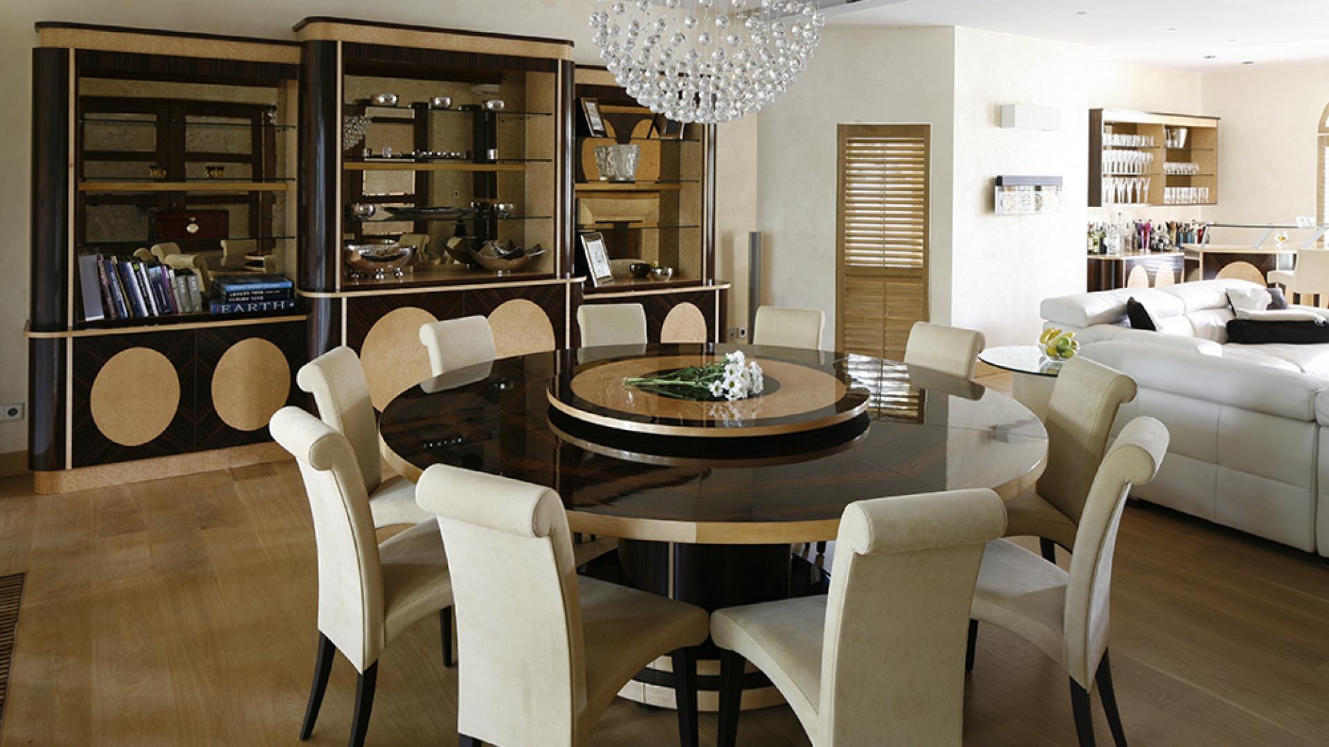 Otwarty na gości salon łączy strefę jadalnianą, wypoczynkową i rozrywkową. Jego funkcję podkreśla okrągły stół, okolony przez stylowe krzesła. Wyrafinowaną elegancję wydobywa przeszklony regał – całość wykonana na zamówienie. Fot. Bartosz Jarosz.