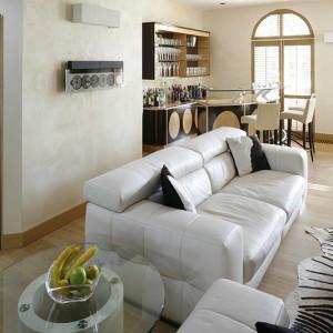 Białe skórzane kanapy (marka) usytuowane w centrum salonu kreują tę przestrzeń na swoistą oazę spokoju. Subtelnie kontrastując z klasycznym brązem wnoszą odrobinę romantyczności w te pełne życia wnętrze. Fot. Bartosz Jarosz.