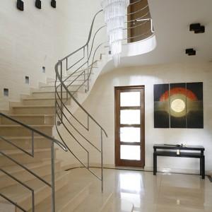 Jasnym, alabastrowym schodom wykonanym z marmuru lekkości dodają zaokrąglone kształty. Satynowane srebrne poręcze, niczym wytworna kolia – wieńczą całość. Fot. Bartosz Jarosz.