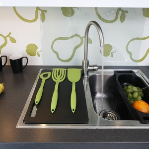 Tapetę w kuchennej przestrzeni między szafkowej przesłaniają szklane tafle, zamontowane jedynie w miejscach niezbędnych, np. przy zlewozmywaku. Fot. Bartosz Jarosz.