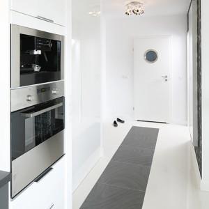Częściowo otwarta na salon, minimalistyczna kuchnia została urządzona szafkami i wyposażona w sprzęt AGD (zlew, piekarnik, okap, ekspres do kawy, lodówka) skompletowany została w IKEA. Fot. Bartosz Jarosz.