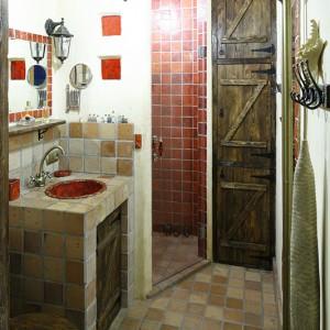 Całe wnętrze prysznica zostało wyłożone szkliwionymi czerwonymi płytkami z wypalanej gliny z autorskiej pracowni Dolo. Drewniane fronty szafek to rękodzieło Michała. Fot. Bartosz Jarosz