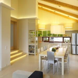 Przestrzeń, na której zaplanowano kuchnię oraz jadalnię, ma imponującą kubaturę, głównie ze względu na wysokość. Przytulny klimat zapewnia ciekawe i efektowne rozwiązanie: podświetlony gzyms na wysokości ok. 3 m oraz jaśniejszy kolor ścian  powyżej. Fot. Bartosz Jarosz.