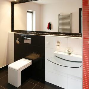 Czerń i biel budują chłodny lecz elegancki charakter niewielkiej łazienki. Duże lustro optycznie powiększa jej przestrzeń, a lakierowana, klasyczna rama przełamuje surowy wystrój wnętrza. Fot. Bartosz Jarosz.