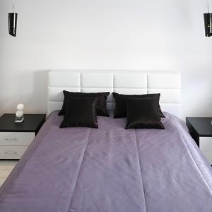Nowoczesne łóżko sypialniane, wykonane z ekoskóry, uzupełniają niskie szafki nocne, których białe szuflady zostały osadzone w czarnej ramie (komplet Fantazja, I-mebel). Tuż nad nimi wiszące czarne lampki ożywiające całą przestrzeń. Fot. Bartosz Jarosz.