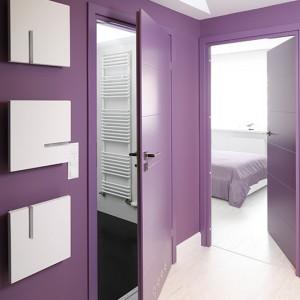 Wrzosowe drzwi płytowe (Pol-Skone) otwierają przejścia do strefy prywatnej: łazienki i sypialni. Pomalowane na ten sam odcień ściany rozświetlają kinkiety z serii Obraz Kopalnia (Cleoni). Fot. Bartosz Jarosz.