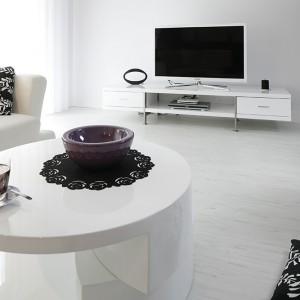 W strefie wypoczynkowej króluje odprężająca biel. Duża, narożna kanapa, mobilny stolik kawowy  oraz niski stolik telewizyjny tworzą minimalistyczny wystrój, podkreślając nowoczesny charakter salonu. Fot. Bartosz Jarosz.