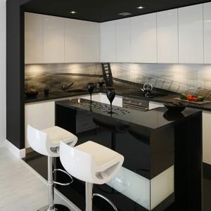 """Podwieszany, lekko opuszczony sufit oraz duże, czarne płytki na podłodze zamykają kuchnię w """"czarną kostkę"""", wyznaczając granicę między strefą kuchenną a salonową. Podkreśla ją bar, którego kształt odtwarza plafon wbudowany w sufit. Fot. Bartosz Jarosz."""