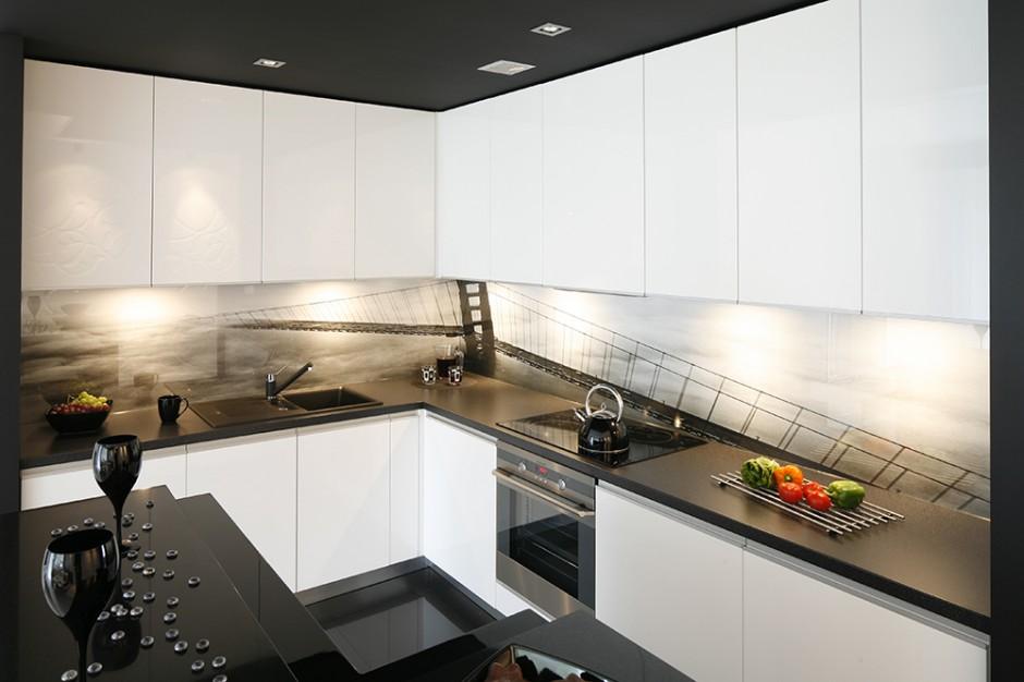 Czarną oprawę zamkniętej w formie kostki kuchni rozświetlają białe fronty szafek. Niebanalny design podkreśla umieszczona w miejscu tradycyjnej glazury fototapeta zabezpieczona szkłem. Fot. Bartosz Jarosz.