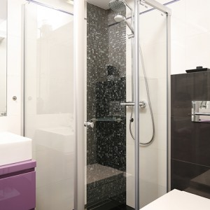 W łazience tradycyjną wannę zastępuje nowoczesna kabina prysznicowa (Hüppe). W jej rogu, jako swoisty dekor, ułożona została czarna mozaika szklana (Miraż). Duże, prostokątne białe płytki (Paradyż) symetrycznie współgrają z czarnymi (Tubądzin), całość wieńczy długa listwa szklana (Tender Rosa, Paradyż) w odcieniu fioletu. Fot. Bartosz Jarosz.