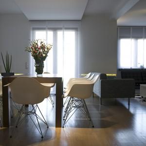 Rozkładany stół w okleinie orzechowej to centralny punkt jadalni. Jego prostotą formę wzbogacają krzesła DAW Plastic Chair. W tyle widoczne dwa czarne fotele Barcelona - ziszczone marzenie pani Justyny. Fot. Małgorzata Opala.