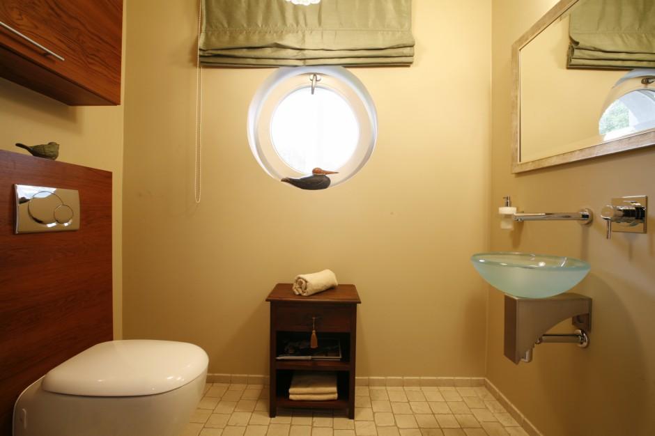 Kształt umywalki (Krzemień) nawiązuje do okrągłej formy okna i łagodnie zarysowanych linii sedesu marki Koło. Podręczna szafeczka doskonale sprawdza się na toaletowe niezbędniki: ręcznik, gazety… Fot. Marcin Onufryjuk.