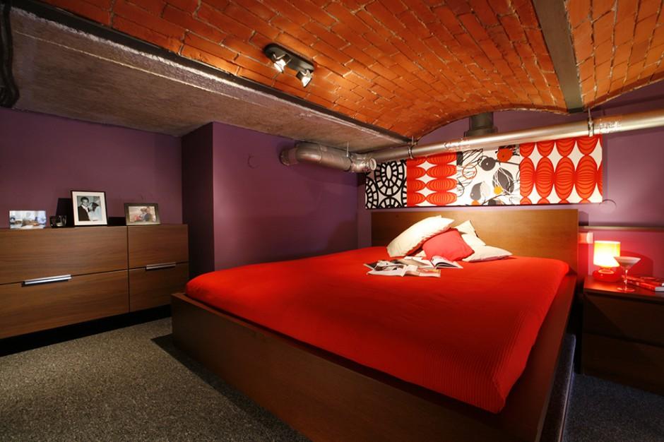 Na ścianach rozlał się zmysłowy fiolet, meble mają odcień mlecznej czekolady, a łóżko otuliła narzuta w kolorze gorącej czerwieni. Fot. Marcin Onufryjuk.