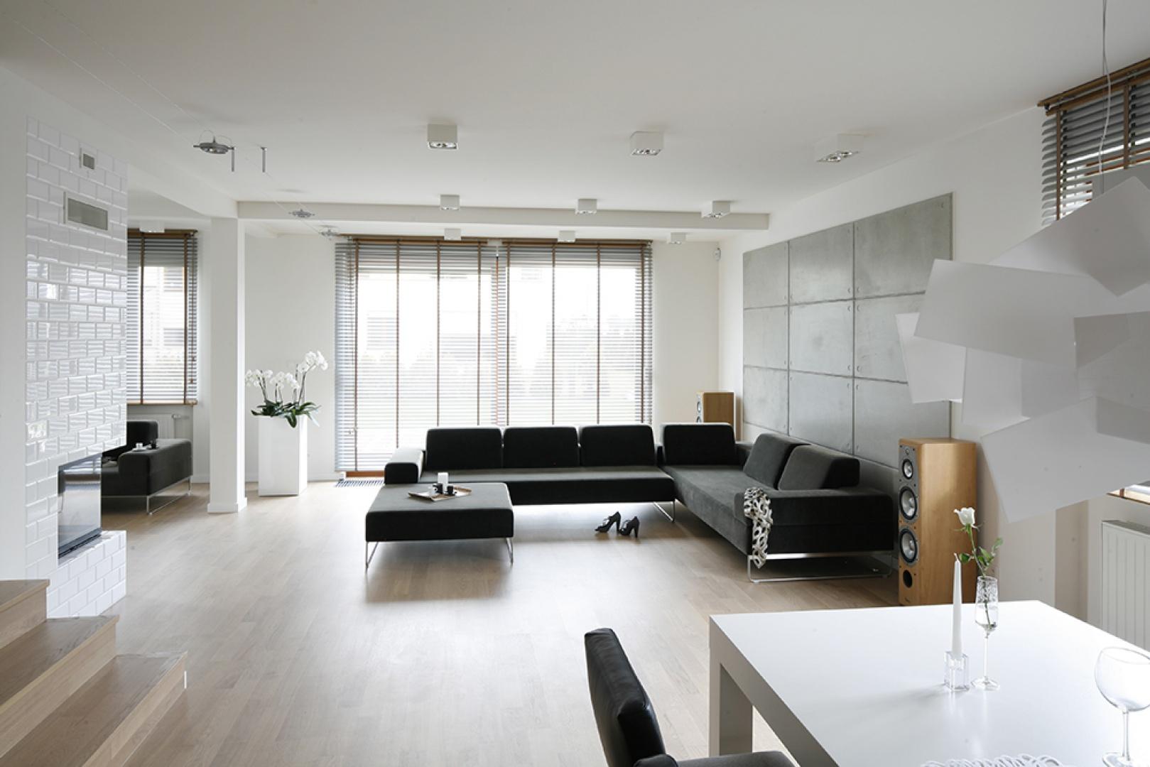 Przestrzeń salonu wypełnia światło, geometryczne kształty i minimalna ilość przedmiotów. Tak skomponowane wnętrze pozostawia w przebywających w nim osobach poczucie głębokiej estetyki. Fot. Bartosz Jarosz.