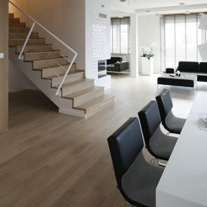 Żelbetowe schody wyłożono bielonym drewnem dębowym i zamontowano białą balustradę w stylu okrętowym. To pomysł pana domu podpatrzony podczas jednej z podróży. Fot. Bartosz Jarosz.