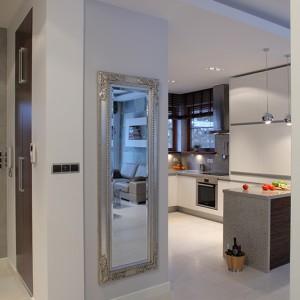 Pani domu urządzając wnętrze z dodatkami w stylu glamour wykazała się dużym wyczuciem smaku, łatwo bowiem popaść w przesadę i stworzyć przeładowane i ciężkie wnętrze. Dekoracyjne lustro przełamuje minimalistyczny i oszczędny wystrój holu. Fot. Bartosz Jarosz.