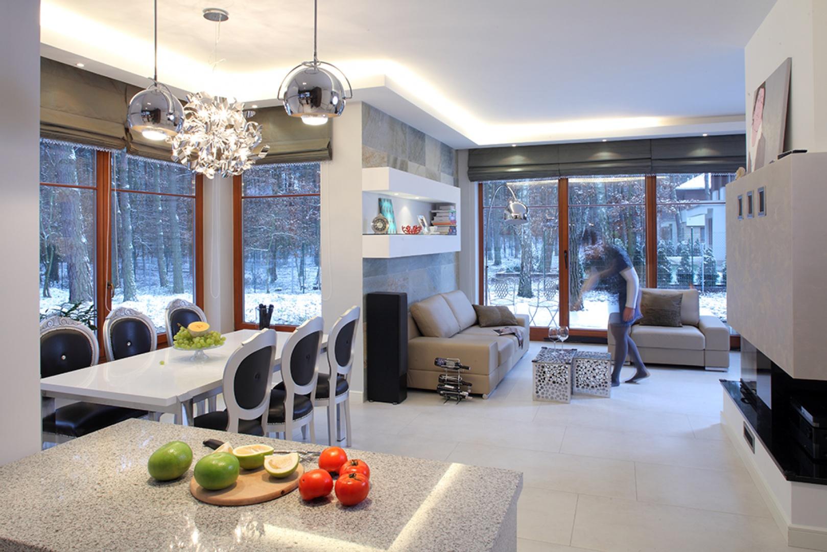 Duże przeszklenia otwierają panoramiczny widok na otaczający las. Kominek w centrum otwartej przestrzeni dzieli salon na dwie części: jadalnianą i wypoczynkową. Jego prostą formę podkreśla czarne granitowe wykończenie w poziomie paleniska. Fot. Bartosz Jarosz.
