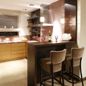 Wykonany z bejcowanego drewna dębowego bar jest kontynuacją obramowania kuchni. Prostą formę dodatkowo podkreślają klasyczne hokery obite tą samą tkaniną, co kanapy w salonie i krzesła w jadalni. Fot. Bartosz Jarosz.