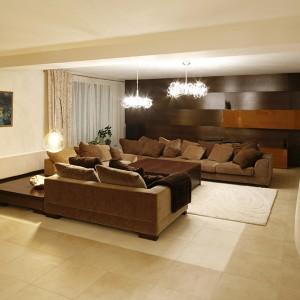Salon miał być z założenia klasyczny. Ciepła przytulność to efekt obecności bejcowanego drewna, kremowej kolorystyki ścian i dodatków oraz miękkiej faktury tkaniny obiciowej na kanapach. Fot. Bartosz Jarosz.