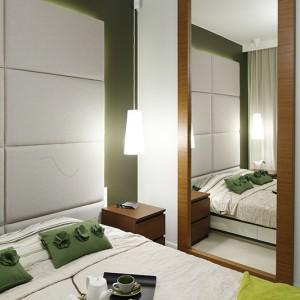 Lustro z drewna teakowego w sypialni to wyraźne nawiązanie do zabudowy kuchennej. Ten sam rodzaj drewna pojawia się na klatce schodowej modernistycznego apartamentowca, stąd pomysł projektantów, aby klimat ten przenieść także do wnętrza mieszkania pokazowego. Fot. Bartosz Jarosz.