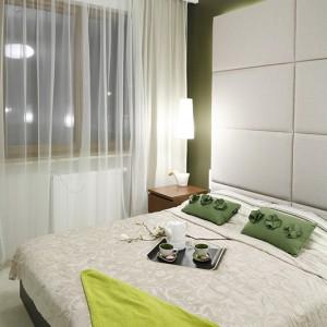 Sypialnia kontynuuje stylistykę pokoju dziennego – rozmyte biele i stonowane zielenie ocieplone zostały mlecznym oświetleniem. Fot. Bartosz Jarosz.