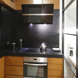 Projektanci zdecydowali się na zabudowę kuchenną pod sam sufit. Pozwoliło to maksymalnie wykorzystać niewielką przestrzeń nowoczesnej kuchni. Fot. Bartosz Jarosz.