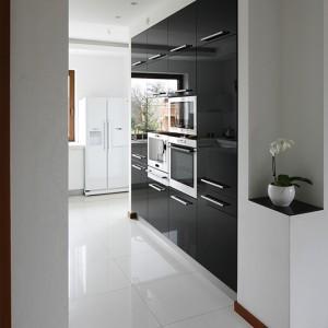 W równie ascetycznej co kuchnia jadalni brak dekoracji, a ograniczenie wyposażenia do minimum rekompensuje ciepło drewnianej podłogi i dyskretny urok czarnych, kryształowych lamp. Fot. Bartosz Jarosz.