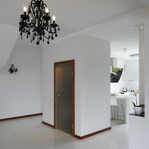 Wyjątkowy klimat domu tworzy nowoczesny wystrój wnętrza oraz ciekawe rozwiązania architektoniczne, jak blok oddzielający kuchnię od holu, w którym urządzono toaletę gościnną. Na ścianach – zarówno od strony kuchni, jak i przedpokoju – tapeta z folkowym wzorem. Fot. Bartosz Jarosz.