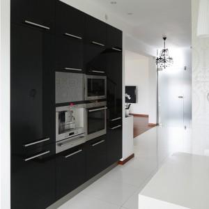 Przeciwwagą dla dominującej bieli jest wysoka zabudowa wykończona frontami z czarnego, lakierowanego MDF-u, oferująca dużą powierzchnię przechowywania. Tutaj umieszczono także nowoczesny sprzęt AGD marki Siemens oraz telewizor. Fot. Bartosz Jarosz.