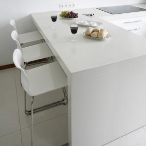 Blaty robocze oraz półwysep kuchenny zostały wykonane z kompozytu marki DuPont™ Corian®. Półwysep pełni także funkcję baru śniadaniowego, przy którym można zasiąść na hokerach wybranych z oferty IKEA. Fot. Bartosz Jarosz.