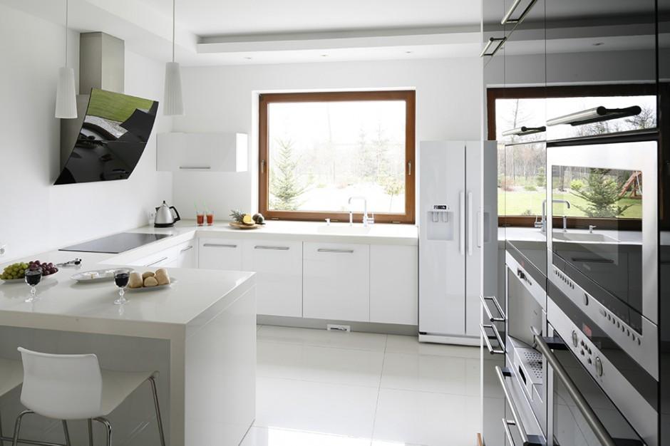 Nowoczesny charakter wnętrza podkreślają fronty szafek z lakierowanego MDF-u, kompozytowe blaty oraz sprzęty: czarny okap przyścienny (Faber) oraz biała lodówka side by side (Samsung). Fot. Bartosz Jarosz.