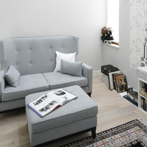 Chwile wytchnienia przy dobrej lekturze zapewnia antresola zwygodną sofą iprywatnym księgozbiorem. Utrzymana wpastelowych odcieniach szarości, otwarta na poziom parteru – zachęca do odpoczynku. Fot. Bartosz Jarosz.