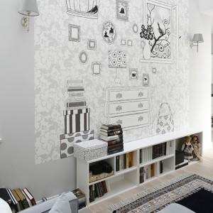 Lekka linia sofy nadaje znajdującej się na piętrze antresoli kobiecego charakteru. Podkreślony jest on kolekcją lalek będącą własnością pani domu oraz licznymi kwiatami iosobistymi drobiazgami. Fot. Bartosz Jarosz.
