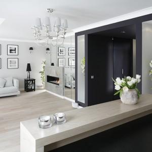 Kuchnia jest scalona z salonem, co podkreśla wspólna kolorystyka oraz styl obu stref. Wizualnie przestrzeń łączy w całość oryginalny portal z wnękami dekoracyjnymi po obu stronach – kuchni i salonu. Fot. Bartosz Jarosz.