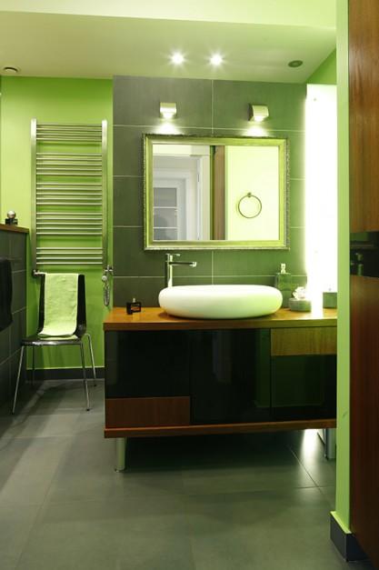 Na pierwszym planie szafka z umywalką oraz lustro, umieszczone na tle ściany działowej wyznaczającej strefę kąpielową. Podświetlony, szklany panel po prawej stronie ścianki wizualnie równoważy wejście do kabiny prysznicowej usytuowane po lewej stronie. Fot. Bartosz Jarosz.