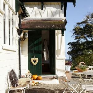 Nowi właściciele postanowili pozostawić drewniany budynek dawnej szkoły pomalowany w tradycyjne kolory – kremowy i zielony. Stylizowana ławka i krzesła zostały kupione na pobliskim targu staroci. Fot. Brent Darby/Narratives.