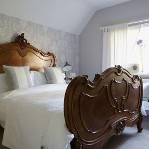 W sypialni dla gości króluje ogromne łoże w stylu Ludwika XV, kupione na internetowej aukcji. Biała bawełniana narzuta i lniane zasłony świetnie się z nim uzupełniają. Fot. Brent Darby/Narratives.