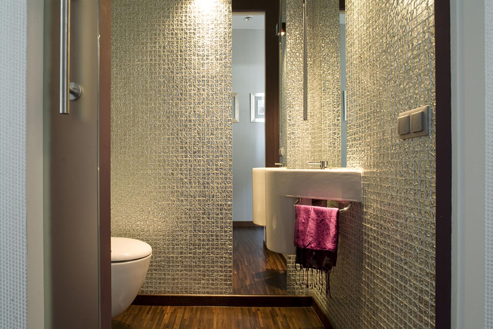 Ściany wykończono lśniącą, lustrzaną mozaiką. Powierzchnię ścian przecinają wąskie, wysokie lustra. Tak jak w pozostałych pomieszczeniach, na podłodze położono parkiet z drewna egzotycznego wenge. Fot. Marcin Onufryjuk.