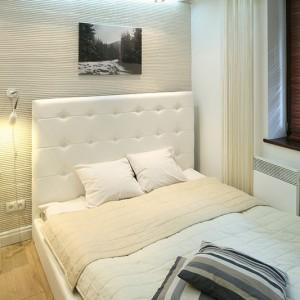 Eleganckie w formie białe łóżko wykonane z ekoskóry i lustrzana rama, zachwycająca ornamentami, wprowadzają do maleńkiej sypialni akcent glamour. Na ścianach autorskie zdjęcia właściciela utrzymane w czarno białej kolorystyce, ukazują piękno okolicy. Fot. Bartosz Jarosz.